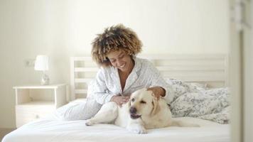 mujer sosteniendo un perro en una cama