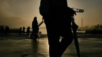 Slow motion of anonymous people on the boardwalk at sunset after a storm. video