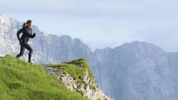 cámara lenta: mujer de pie en el borde de la montaña con las manos en alto video
