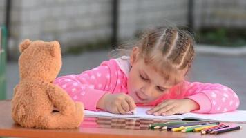 bambina di cinque anni dipinta ordinatamente cancella la matita da gomma nell'album