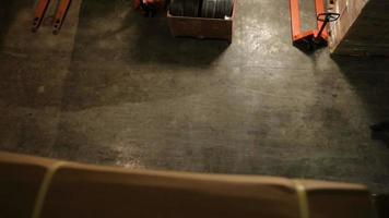 homem move caixas com porta-paletes em armazém de transporte video