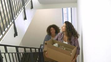 duas mulheres se mudando para uma nova casa carregando uma caixa para cima