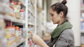 Mujer joven elige comida para bebés en el supermercado.