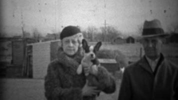 1933: coppia mostra un nuovo cagnolino in abiti invernali formali.