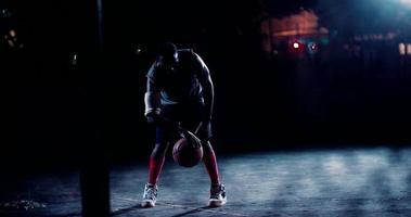 jogador de basquete driblando a bola na quadra à noite