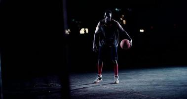 Basketballspieler dribbelt Ball auf dem Platz in der Nacht