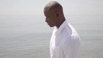 Thoughtful African man walking along the sea video