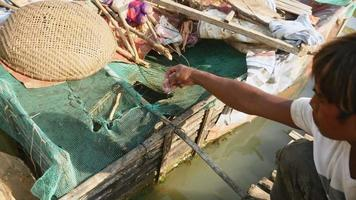 Fish farmer feeding fish in a bamboo crate fixed to a houseboat ( close up )