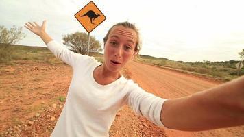 Selfie der jungen Frau in Australien, die nahe Känguruzeichen steht