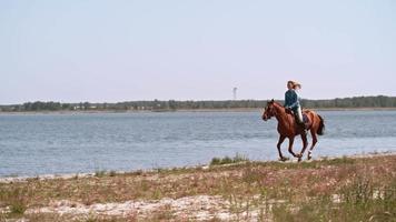 Femme galopant au bord du lac à cheval
