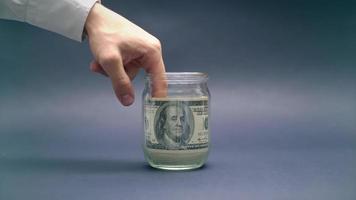 Hand nimmt Geld aus Glas
