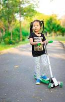 Girl learning to ride a scooter in a park