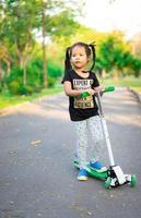 niña aprendiendo a andar en scooter en un parque