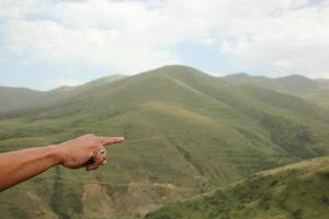 Person pointing finger toward Armenian mountains