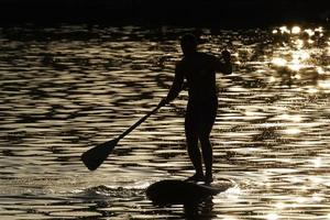 Silhouette of man on a paddle board