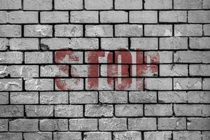 Stop painted on a brick wall