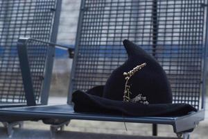 Witch hat with dried flowers left on bus stop