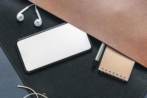 vista superior de una maqueta de teléfono inteligente con artículos en un bolso