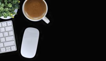 Vista superior del espacio de trabajo con un teclado, mouse y café sobre una mesa negra