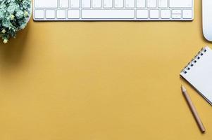 vista superior de uma mesa amarela com teclado e bloco de notas