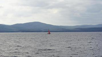 Red sailboat on Lake Ozero Turgoyak