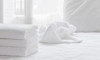 Folded clean towels on a white bed sheet