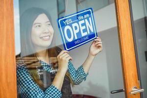 mujer volteando el letrero abierto en una puerta