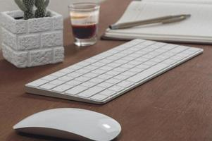 Keyboard, mouse and houseplant with espresso on wooden table