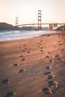 Footprints on sand near Golden Gate Bridge