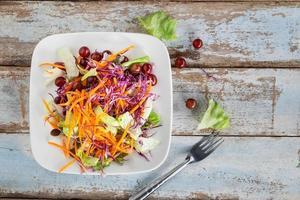 Ensalada de verduras en un recipiente sobre la mesa de madera