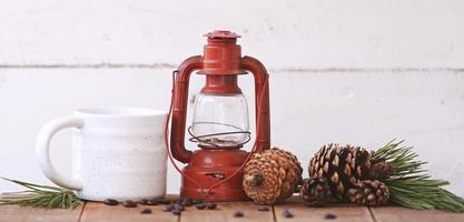 Lantern and a coffee cup with pinecones