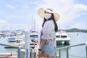 Woman wearing face mask near the dock photo