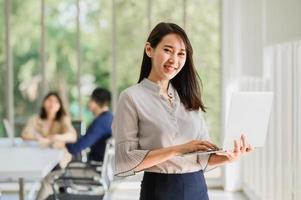 mulher asiática segurando um laptop foto