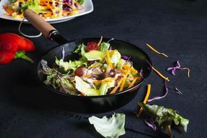 Ensalada de verduras en una sartén sobre fondo negro