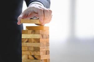 Businessman arranging wood blocks
