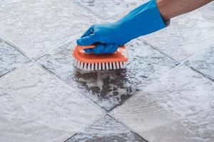 Close-up of person scrubbing a floor