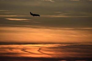 silhouet van een vliegtuig bij zonsondergang