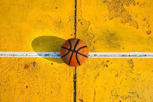 Old basketball on a yellow court