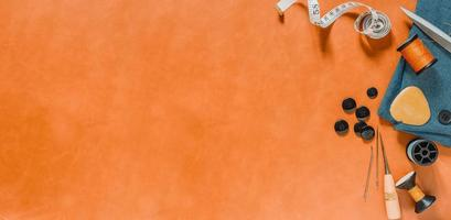 Orange textured background with sewing tools photo