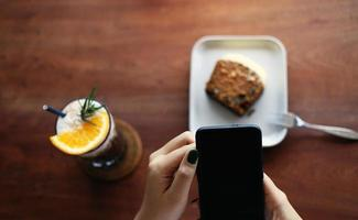 Girl uses mobile phone during coffee break in cafe