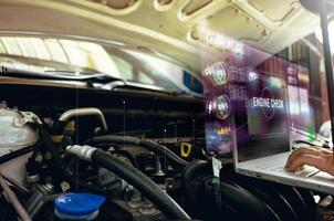 Technician uses laptop to analyze car engine with hologram