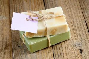 Two natural soap bars with tag on wood