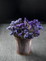 buquê de flores violetas secas em balde velho