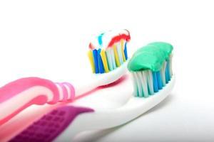 Cepillo de dientes con pasta de dientes sobre un fondo blanco.