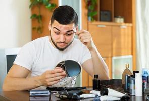 cara removendo o cabelo da sobrancelha