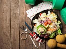Dumbells, tape measure and healthy food salad on wooden backgrou