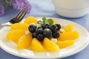 Delicious fruit salad with oranges, blueberries and cream. photo