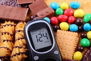 Glucometer with heap of sweets and cane brown sugar