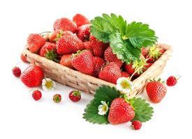 Cesta de fresas frescas con hojas verdes y flores. foto