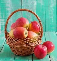 Ripe red apples in a basket on wooden background photo